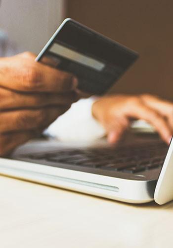 consumer entering credit card information ontop a laptop